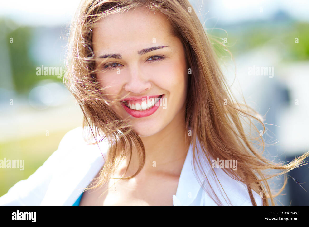 Close-up portrait of a cheerful beauty on a windy day - Stock Image