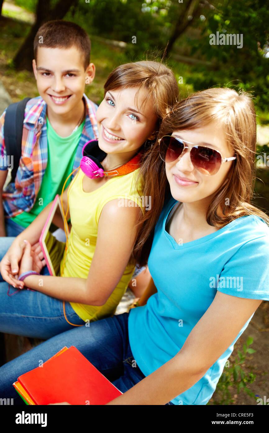Vertical shot of three teens smiling cheerfully at camera - Stock Image