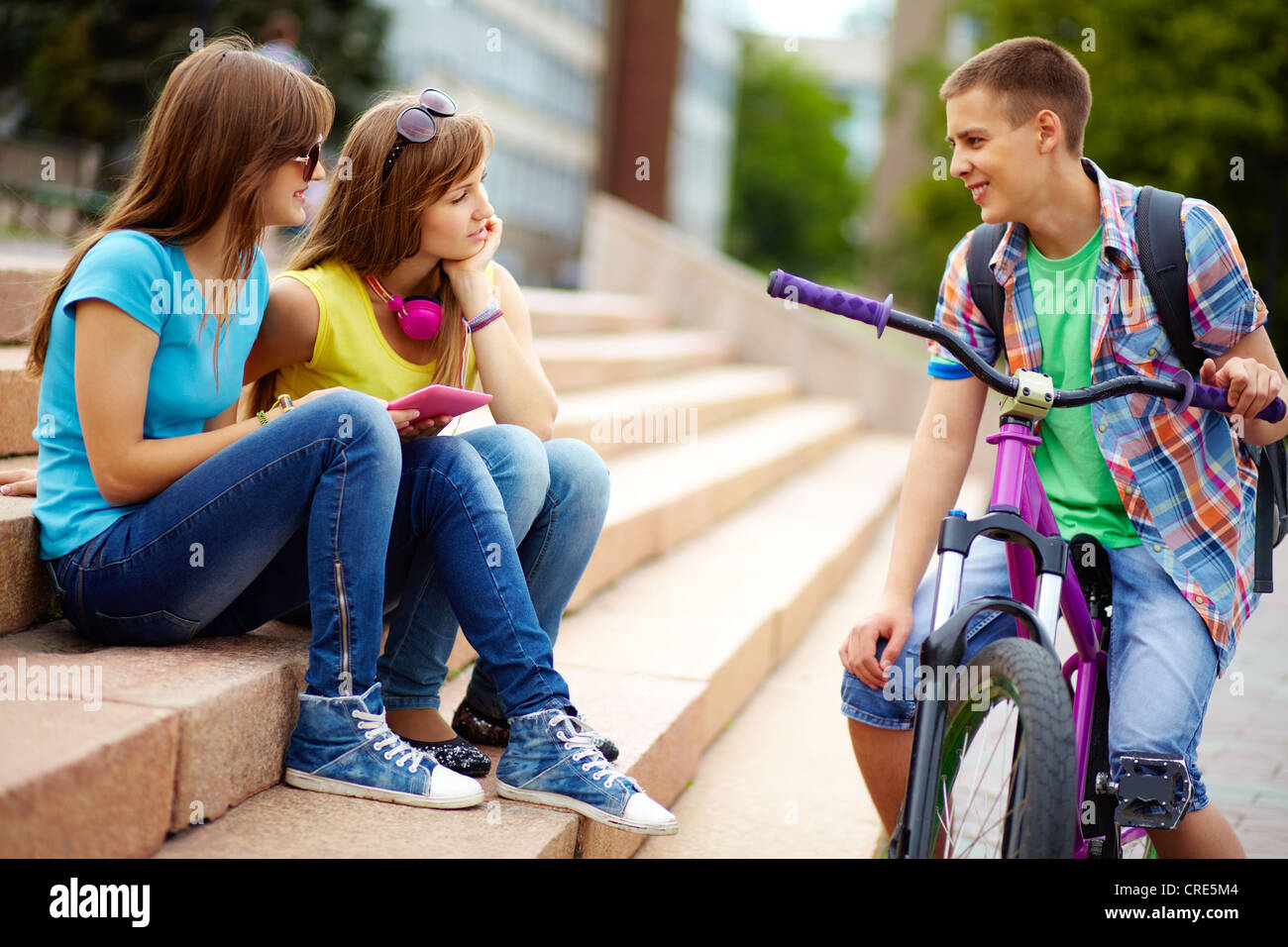 Teen girls seeming to be interested in the guy riding the bike - Stock Image