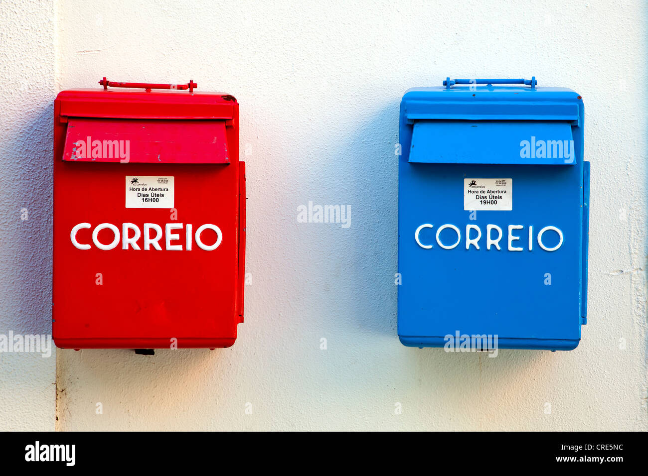 Mailboxes of the Portuguese postal service, Correio, in red and blue for different collection times, in the district - Stock Image