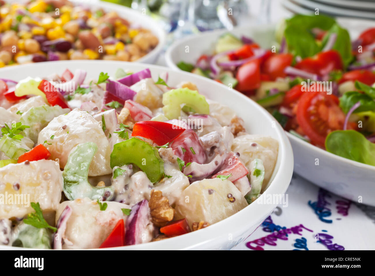 An Assortment Of Salads On A Buffet Table With Party Decorations
