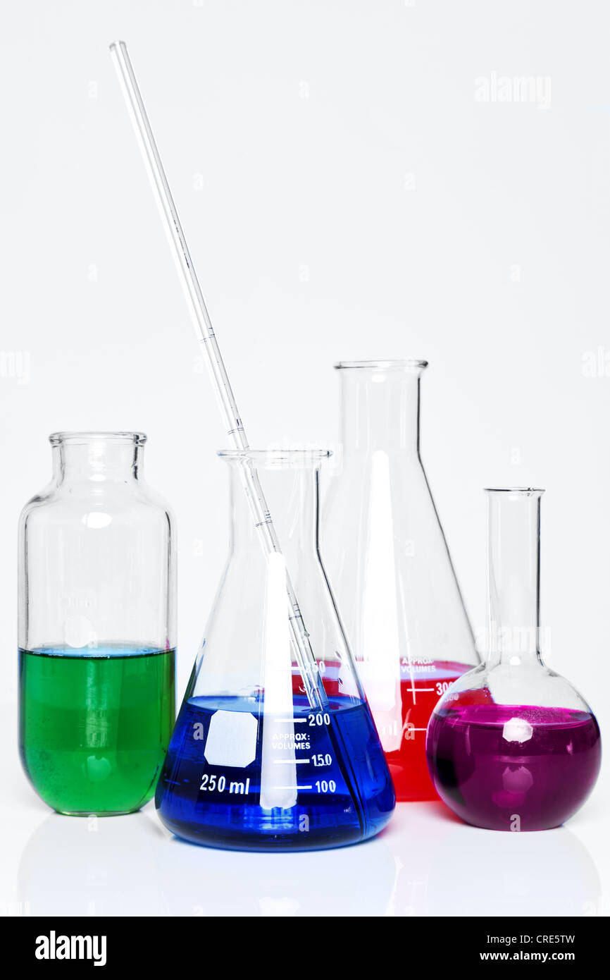 Photo of chemistry flasks full of chemicals on a plain background. - Stock Image