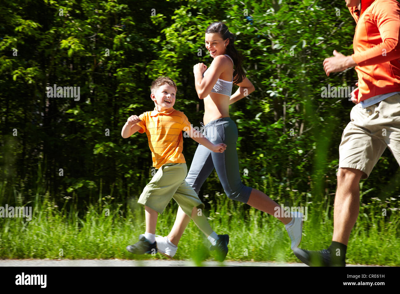 """Happy running family proving the well-known saying """"Life is motion"""" - Stock Image"""