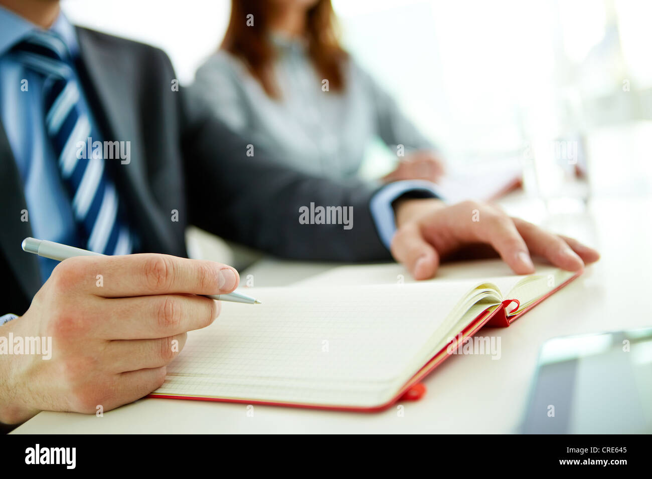 Male office worker making appointments and notes in his organizer - Stock Image