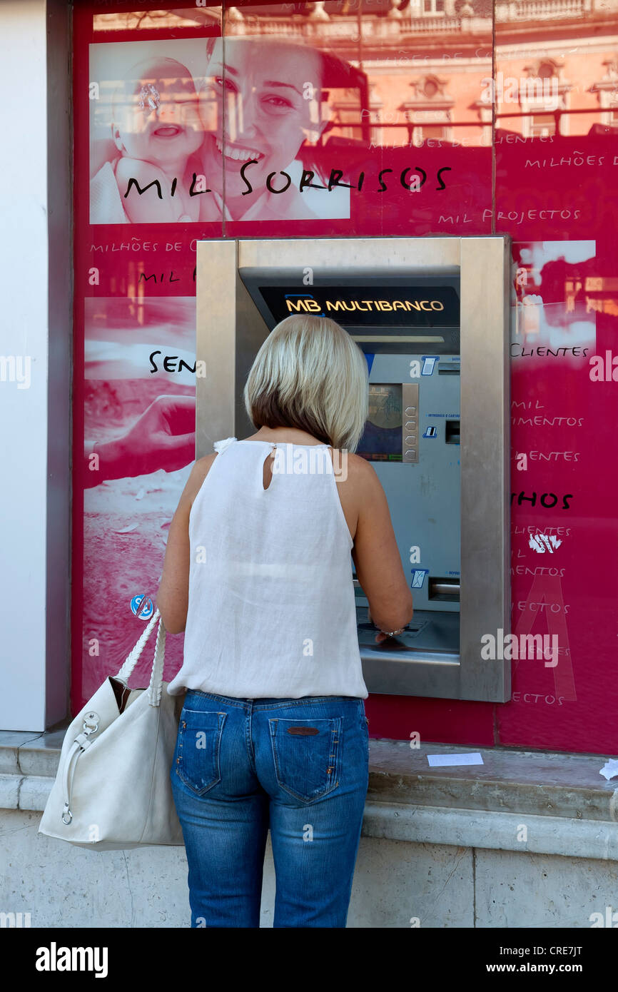 Woman at an ATM at a branch of the Portuguese bank Millennium BCP, Banco Comercial Portugues, Portuguese Commercial - Stock Image