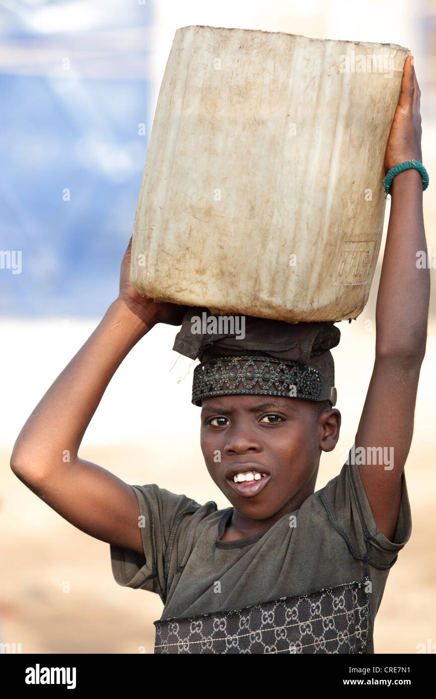 A boy carries a jerrican of water on his head in the Clara Town slum of Monrovia, Montserrado county, Liberia - Stock Image