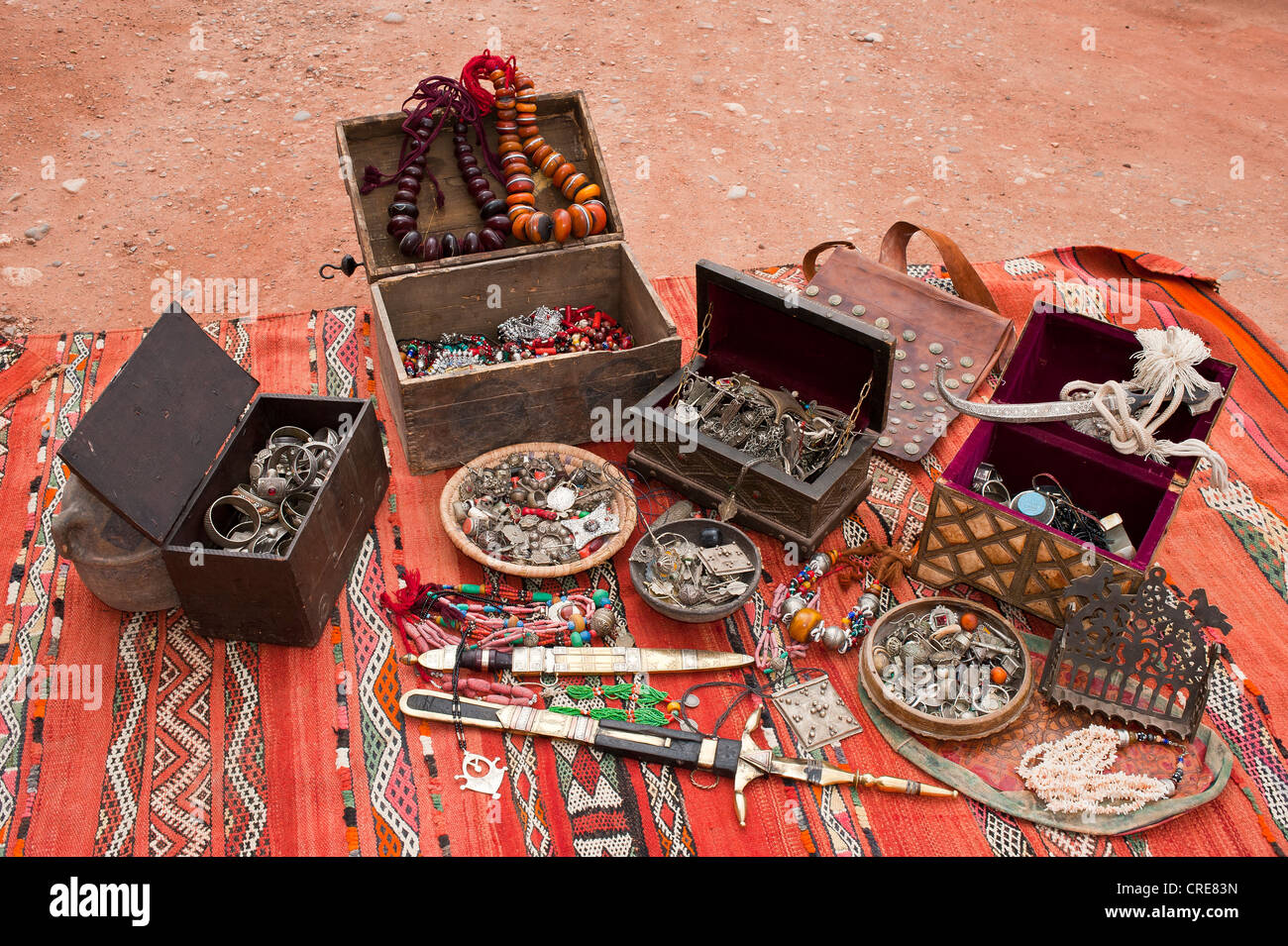 Little treasure chests, traditional oriental jewellery and decorated Touareg knife spread on a carpet, Morocco, - Stock Image