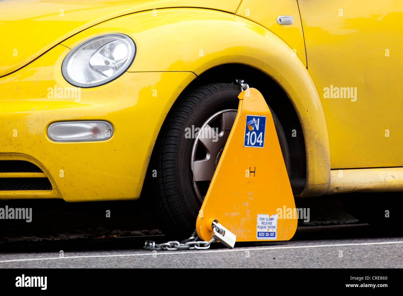 VW Beetle car with a wheel clamp for false parking in Dublin, Ireland, Europe - Stock Image