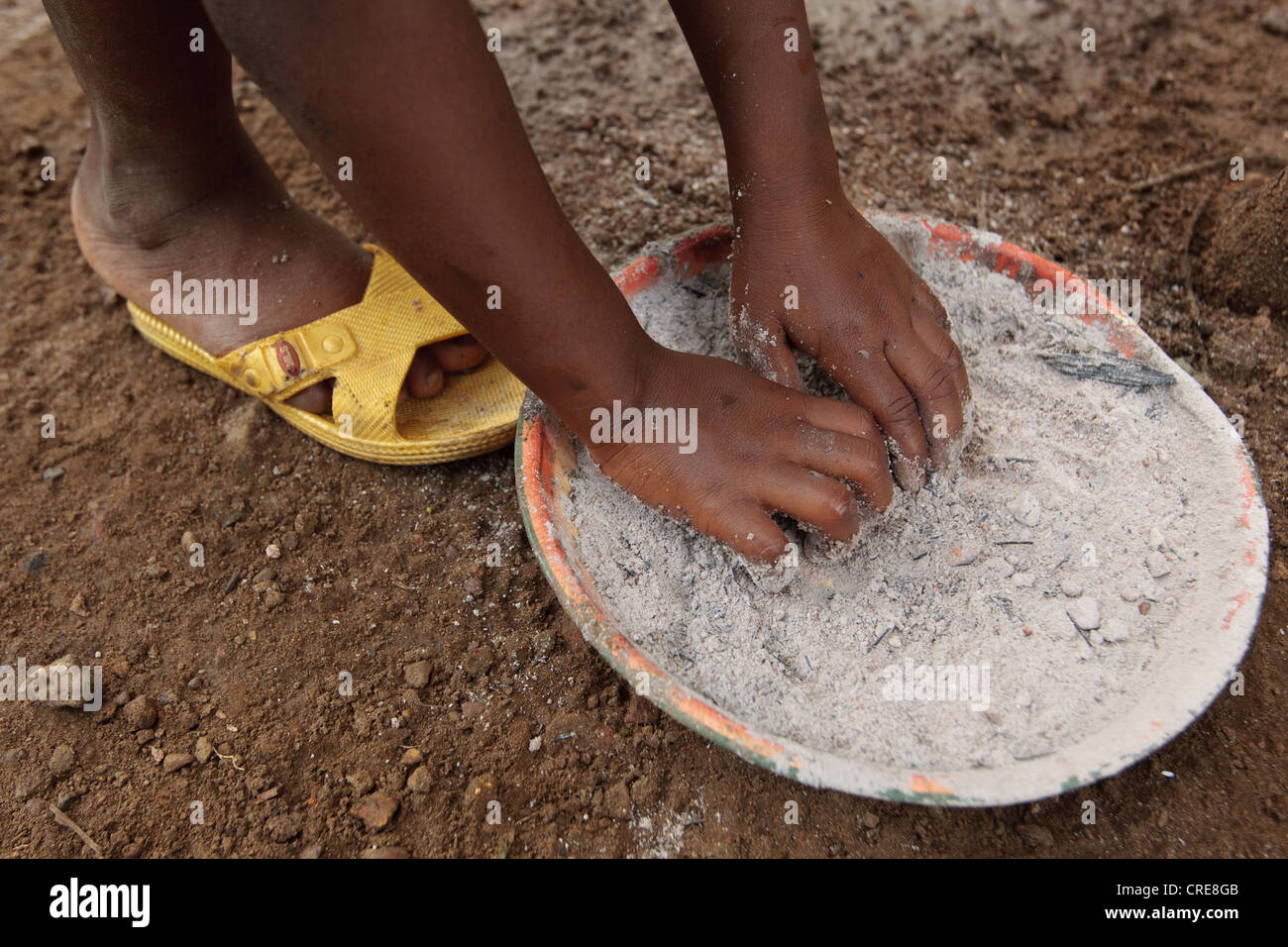 A girl picks up a handful of ash, a substitute for soap, as she washes his hands at a pedal-activated hand washing - Stock Image