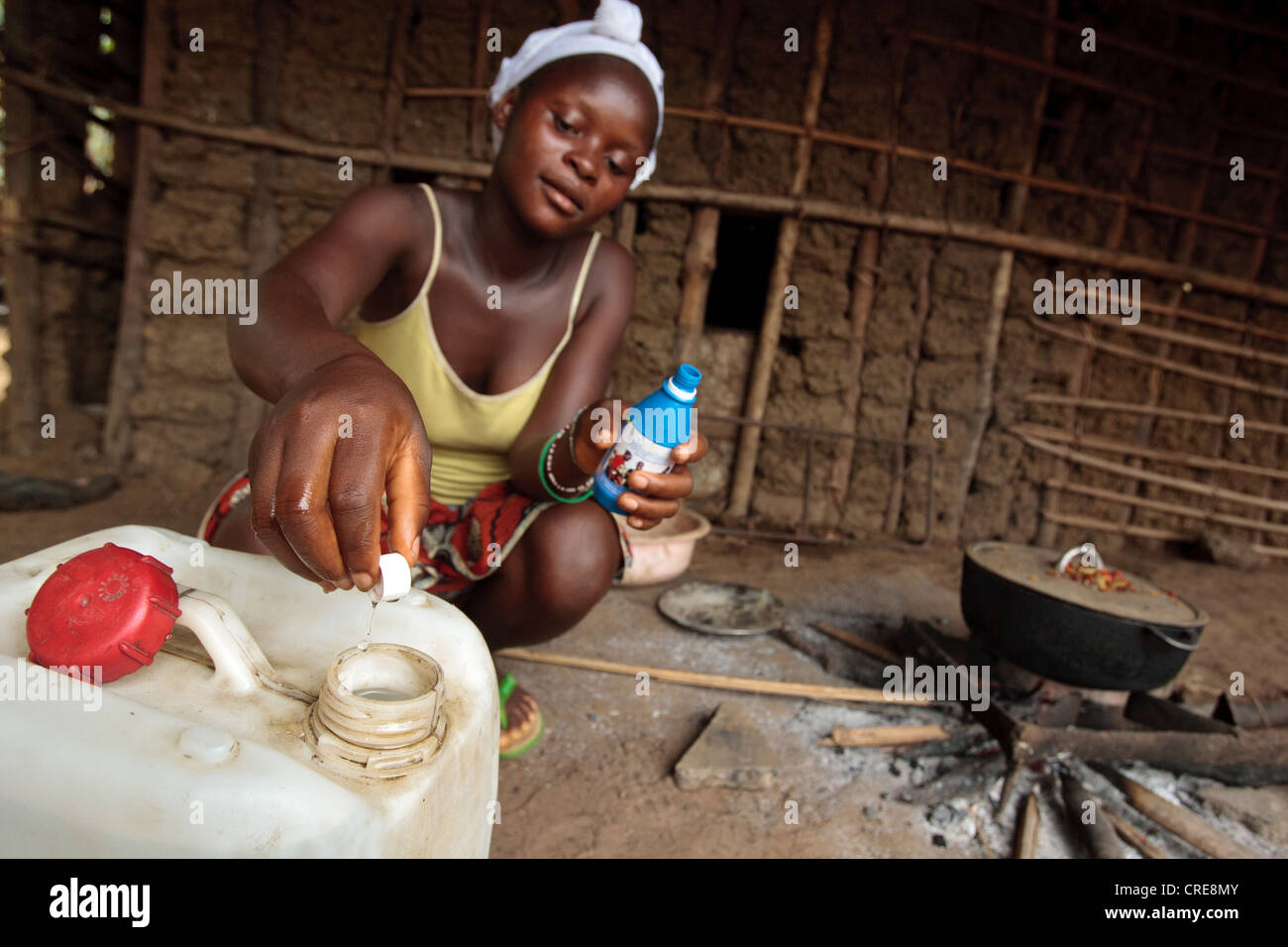 A woman uses a chlorine water treatment product to treat drinking water at home in the village of Kawejah, Grand - Stock Image