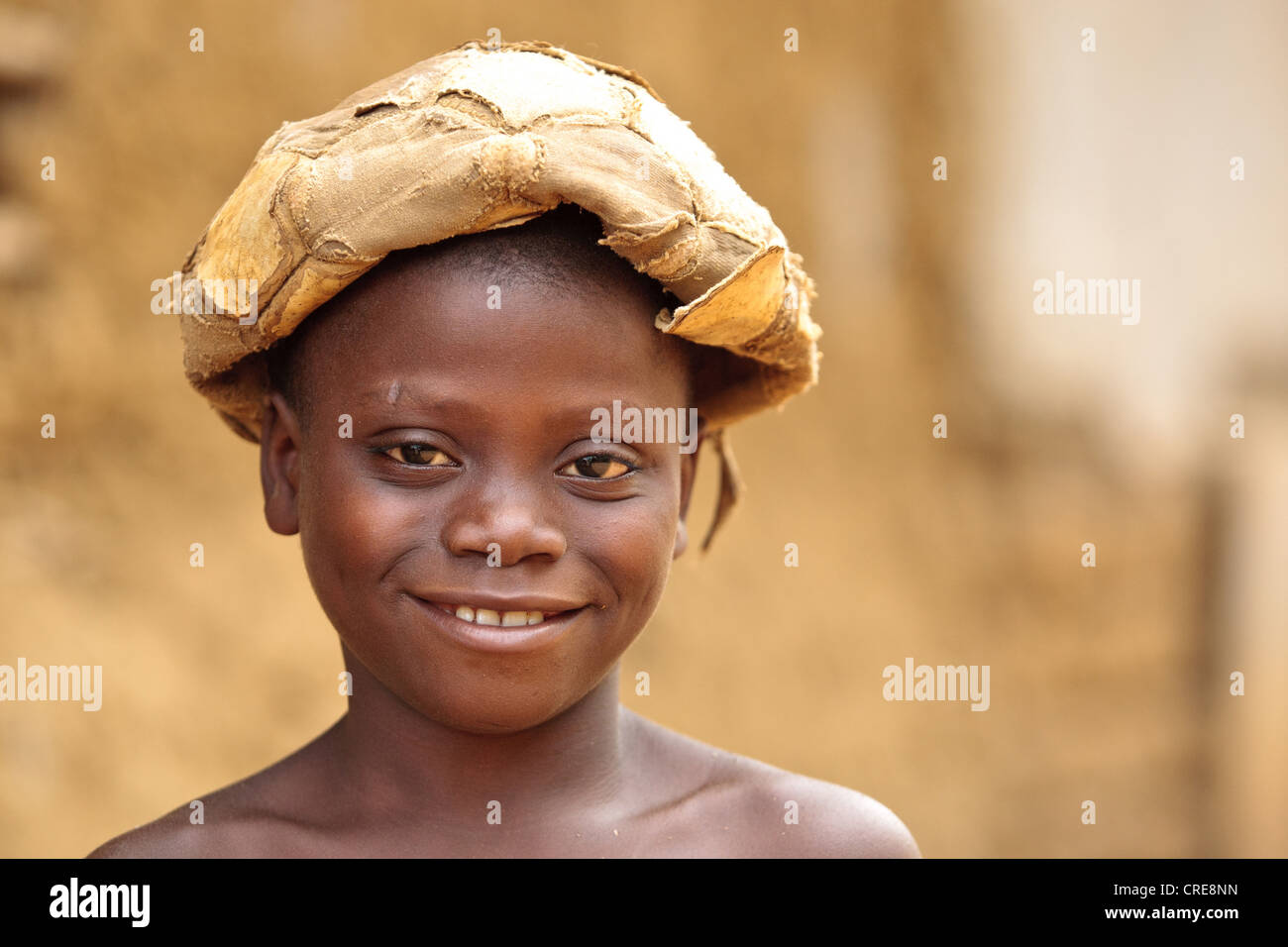 Portrait of a boy with a deflated football on his head in the village of Kawejah, Grand Cape Mount county, Liberia - Stock Image