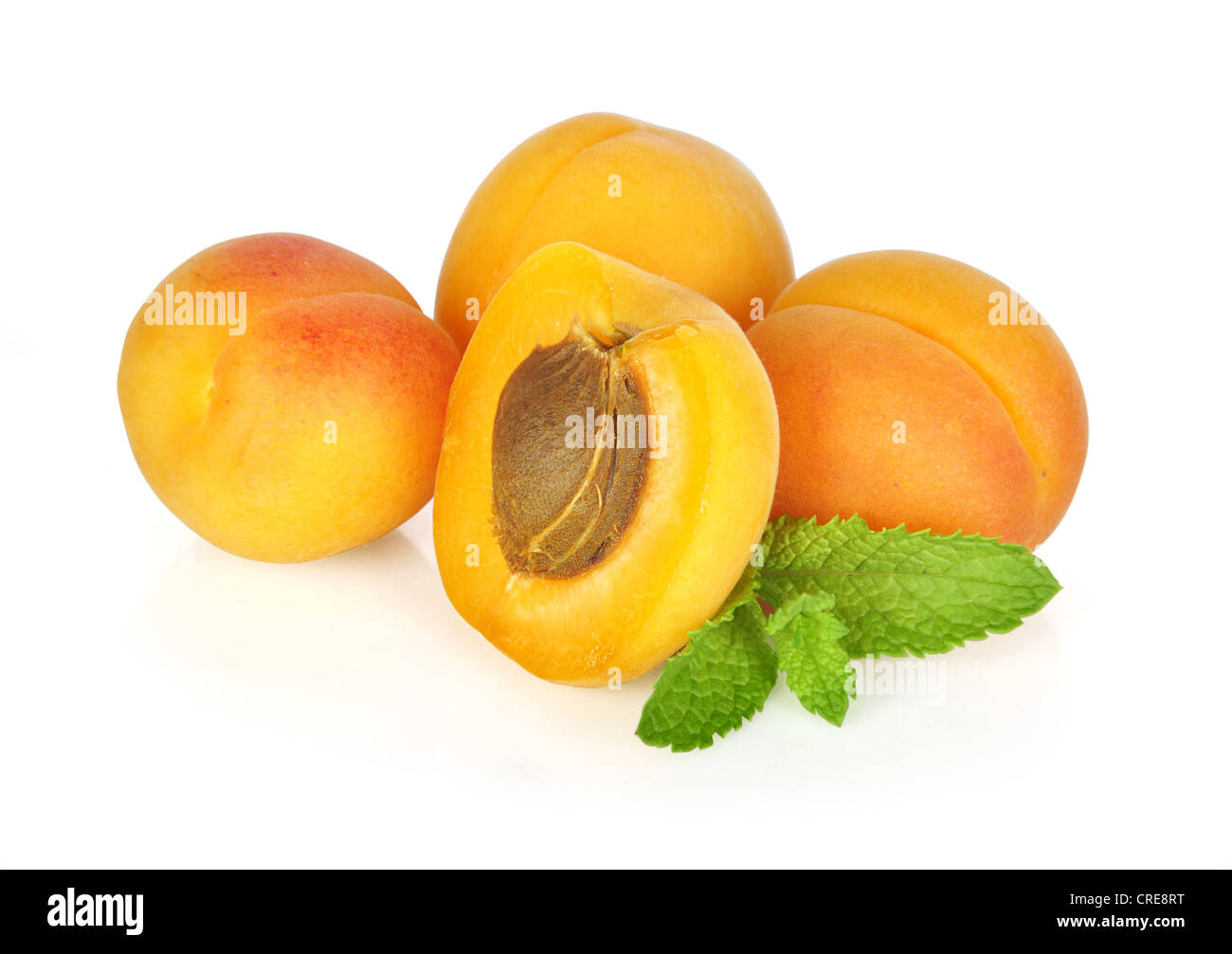 Some apricots with leaves isolated on white background - Stock Image