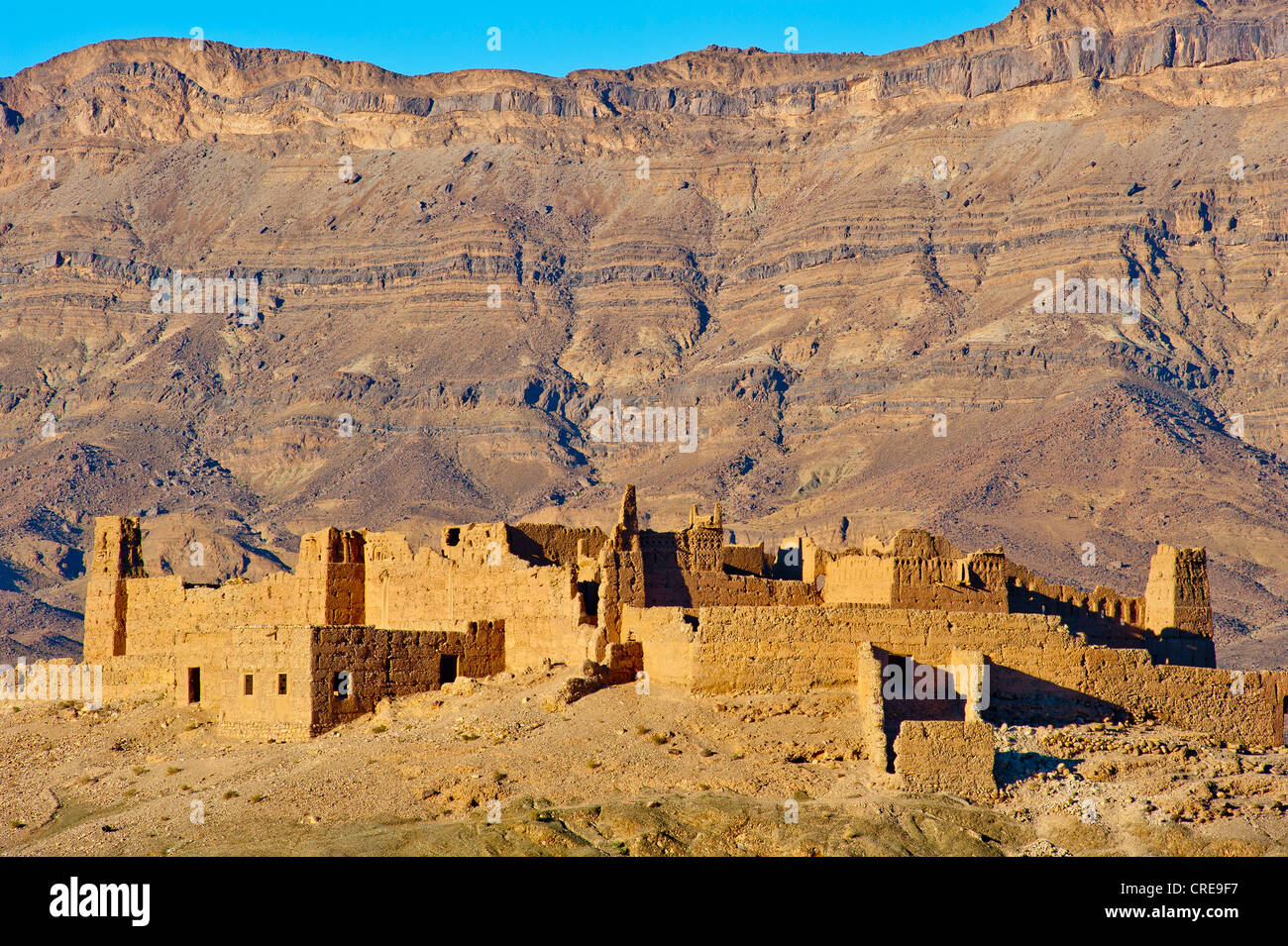 Ruined Kasbah on a hill, a former Berbers' house built of adobe, mountain range of the Djebel Kissane table - Stock Image