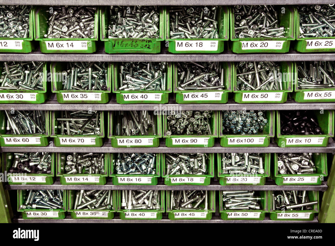 Screws of various sizes in plastic containers on a shelf - Stock Image