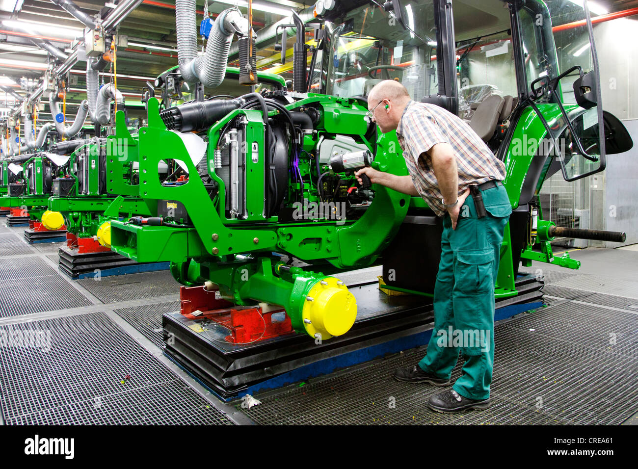 Final inspection, man searching for a leak with a UV lamp in the tractor production section at the European headquarters - Stock Image