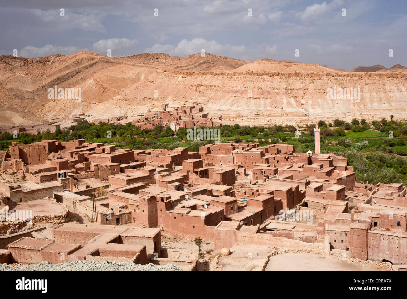 Typical village of mud-walled houses with a mosque and small fields on a riverine oasis, High Atlas Mountains, Morocco, Stock Photo
