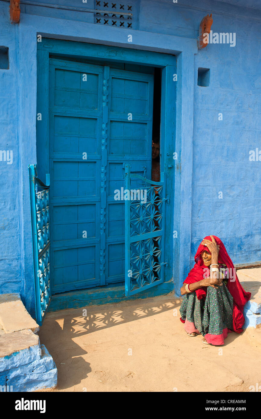 Elderly Indian woman sitting on the floor in front of her blue-painted house, Bishnoi, Jodhpur, Rajasthan, India, - Stock Image