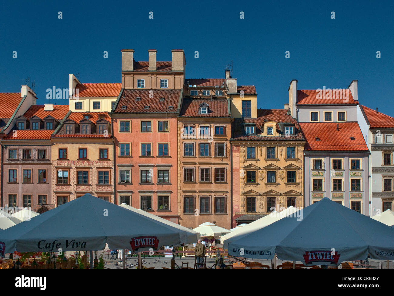 Burghers houses and parasols at open-air cafes in Old Town Market Square in Warsaw, Poland - Stock Image