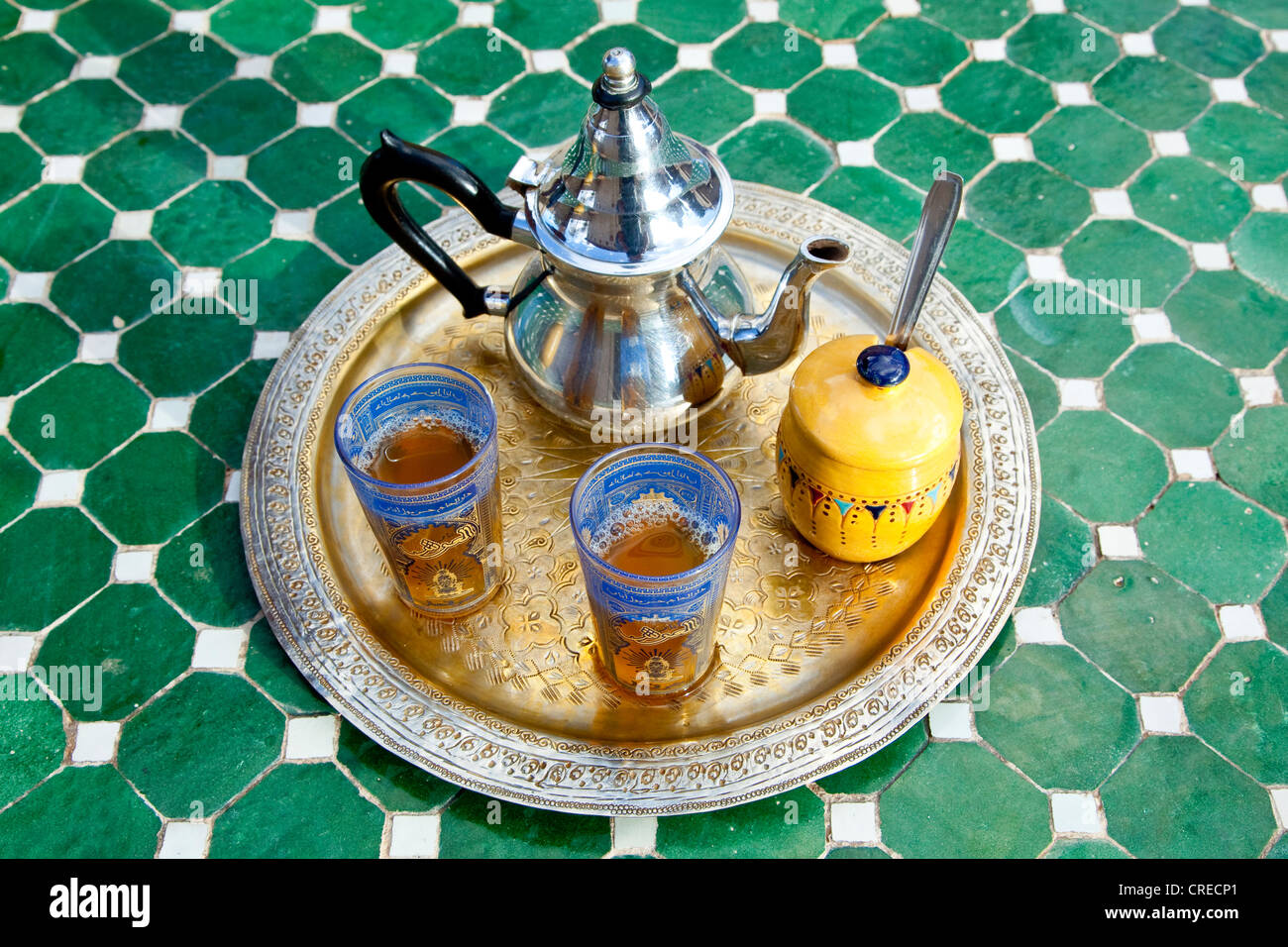 Silver tea pot with mint tea and glasses on a mosaic table in Agdz, Morocco, Africa - Stock Image