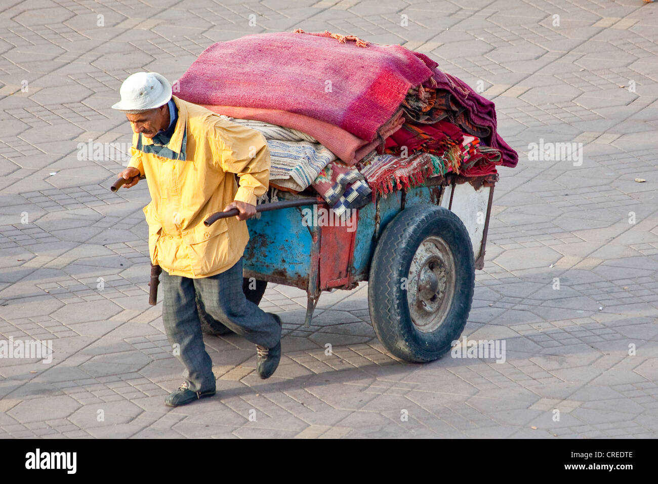 Man transporting carpets with a handcart, Djemaa El Fna square, medina or old town, UNESCO World Heritage Site, - Stock Image