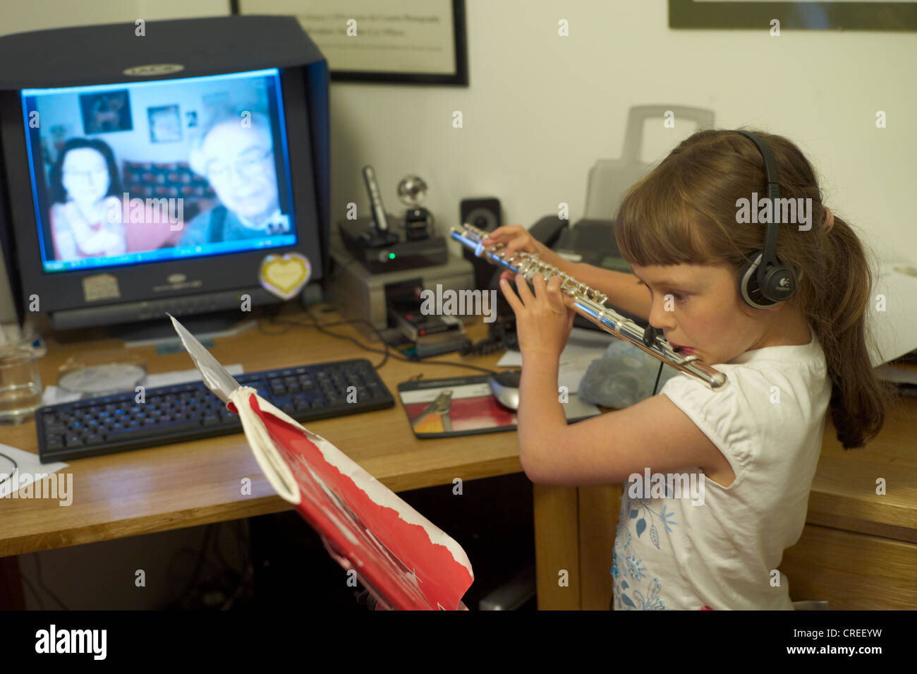 Child playing her flute to her grandparents via Skype - Stock Image