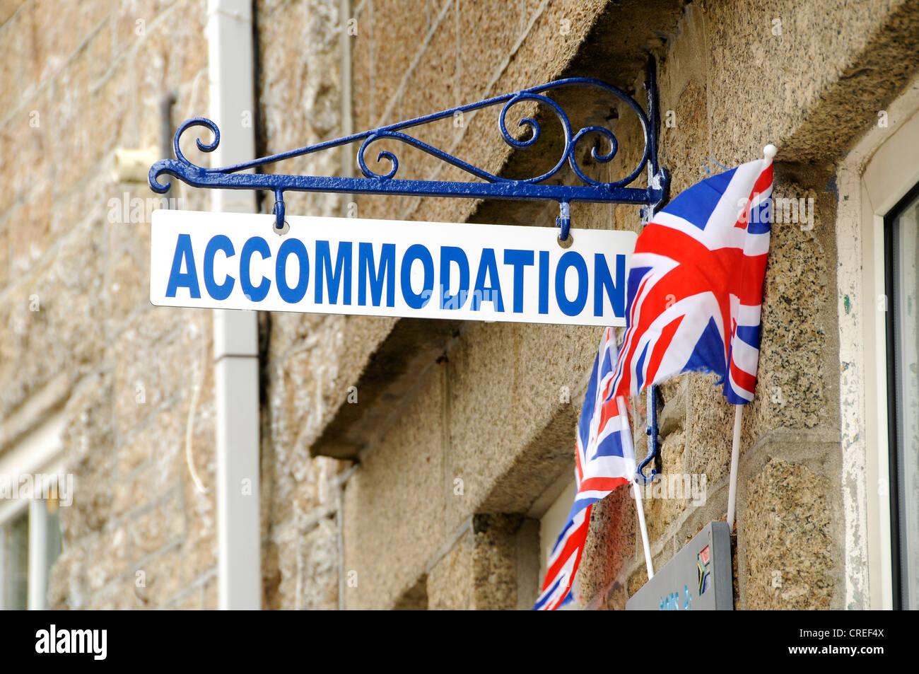Accomodation sign outside a UK seaside hotel with union jack flags as decoration - Stock Image