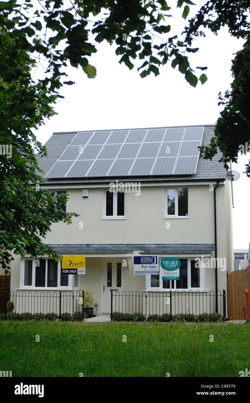 Solar Voltaic panels on new house and house for sale signs at The Limes in Plymouth Devon - Stock Image