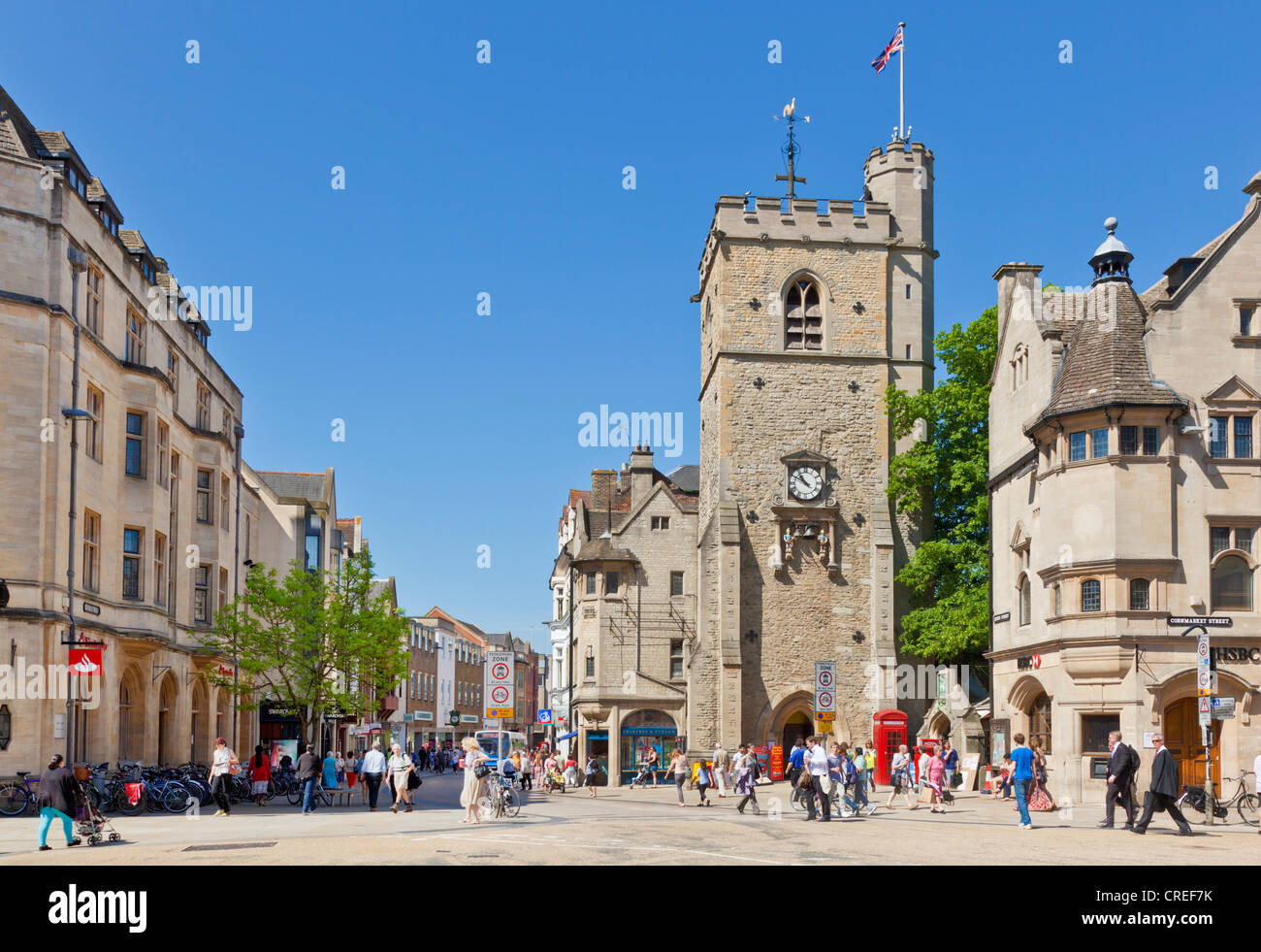 Shoppers in Oxford city centre with Carfax tower at Junction of High street Queen street St Aldates and Cornmarket - Stock Image