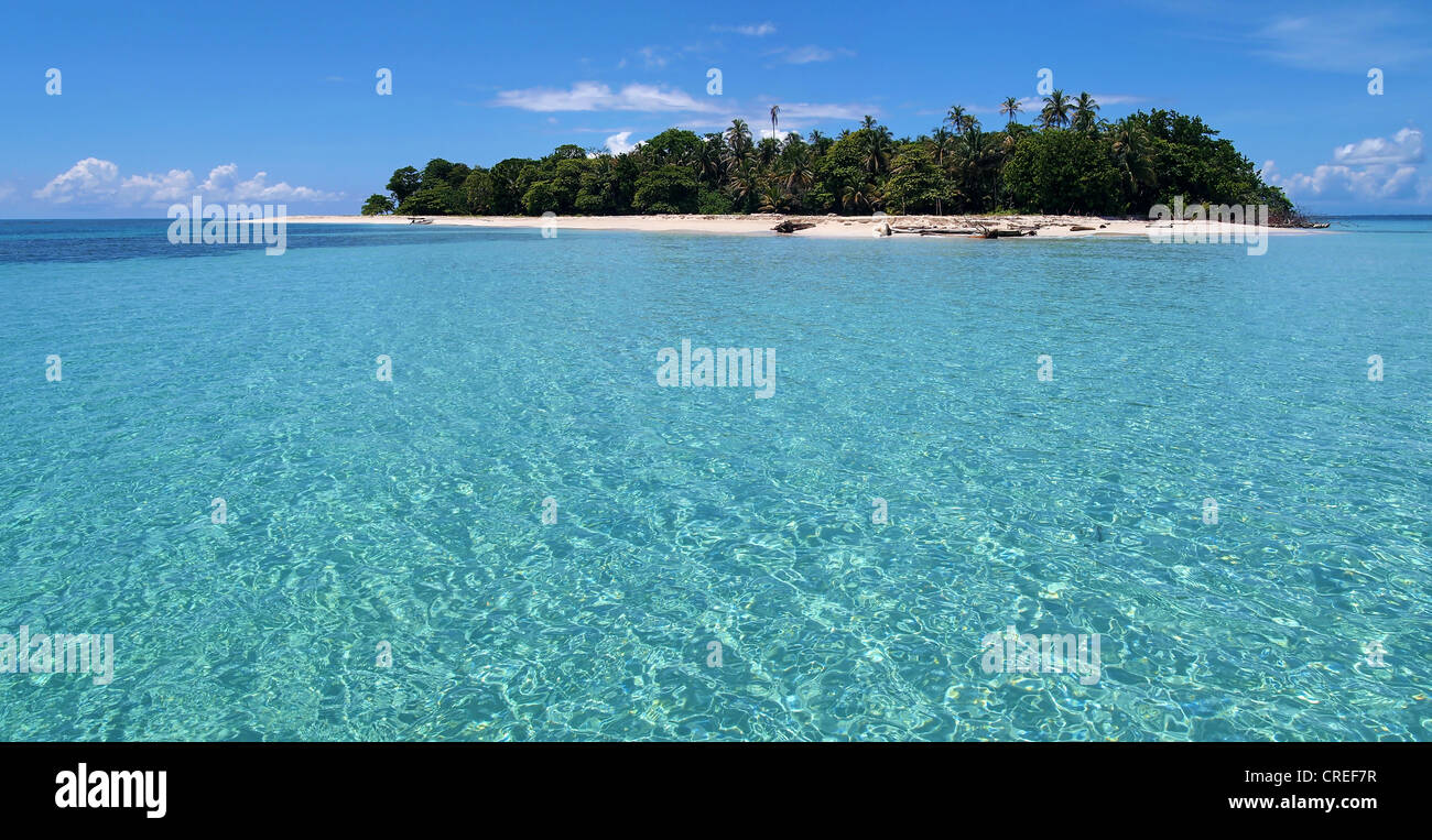 Pristine island with lush vegetation, white sandy beach and a lagoon with turquoise water - Stock Image