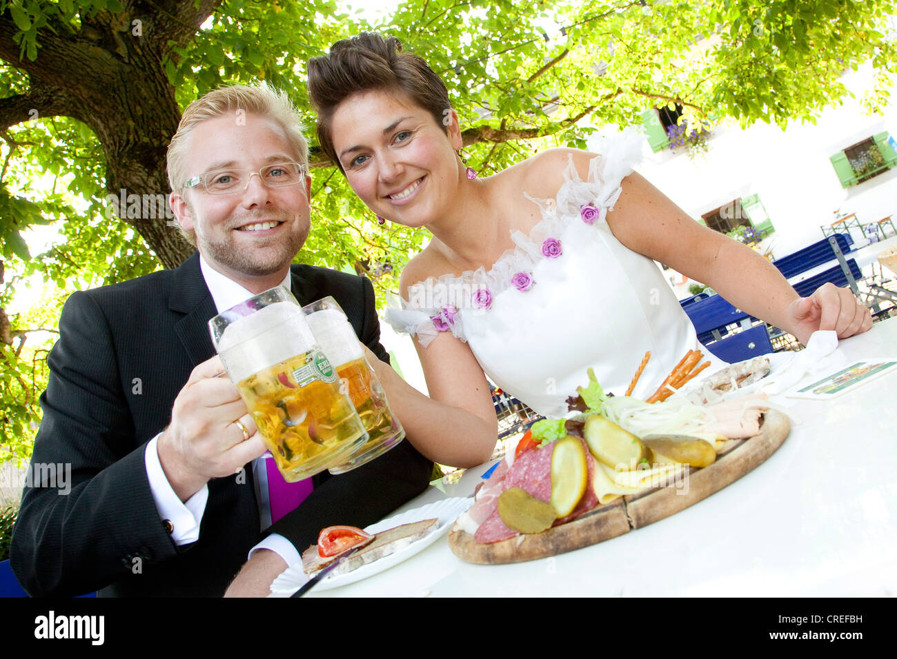 Bridal couple having a light meal and drinking beer in a Bavarian beer garden, Regensburg, Bavaria, Germany, Europe Stock Photo
