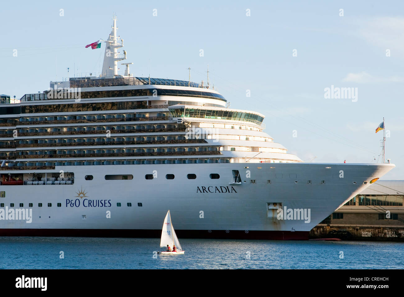 Small sail boat off the cruise ship Arcadia in the marina, Funchal, Madeira, Portugal, Europe - Stock Image