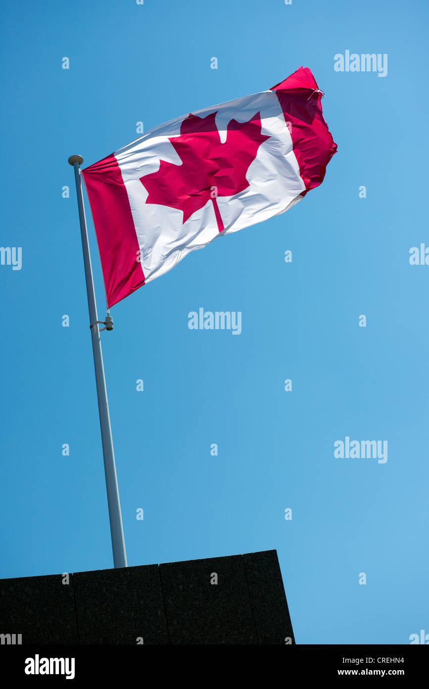 Canadian national flag flying atop aflagpole against a blue sky - Stock Image