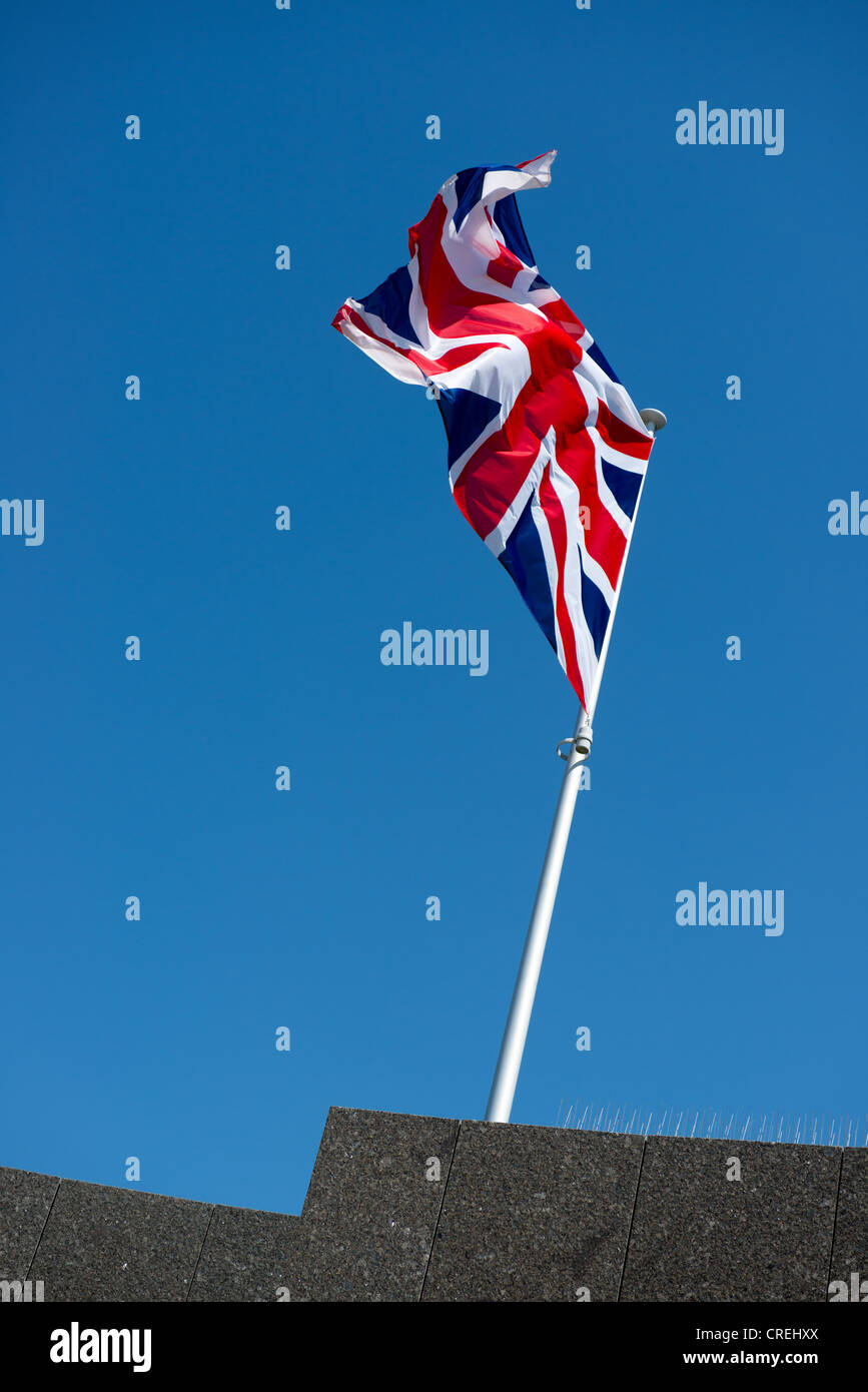 Union flag  on a flagpole flying against a blue - Stock Image