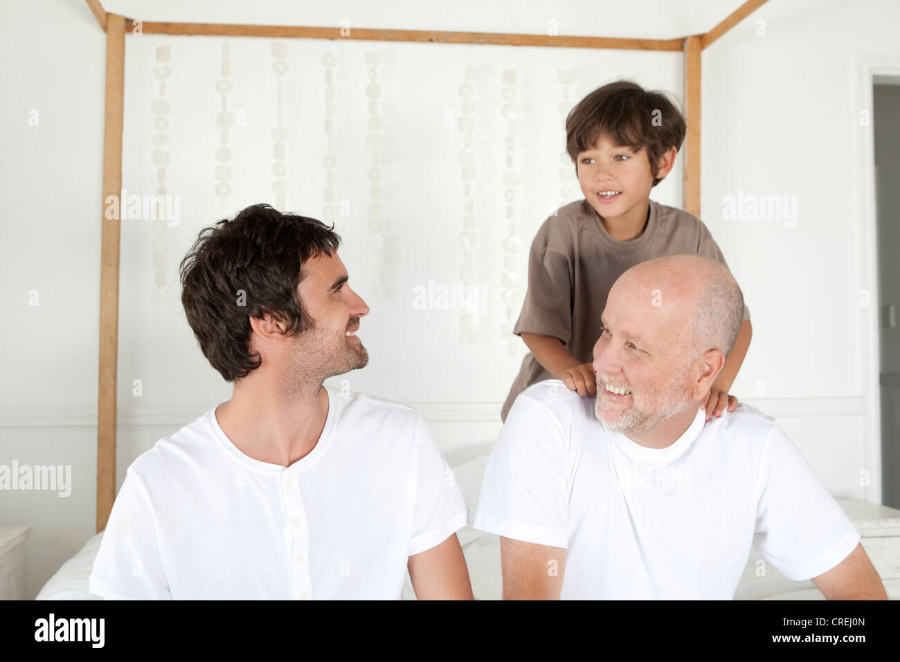 Three generations of men on bed - Stock Image