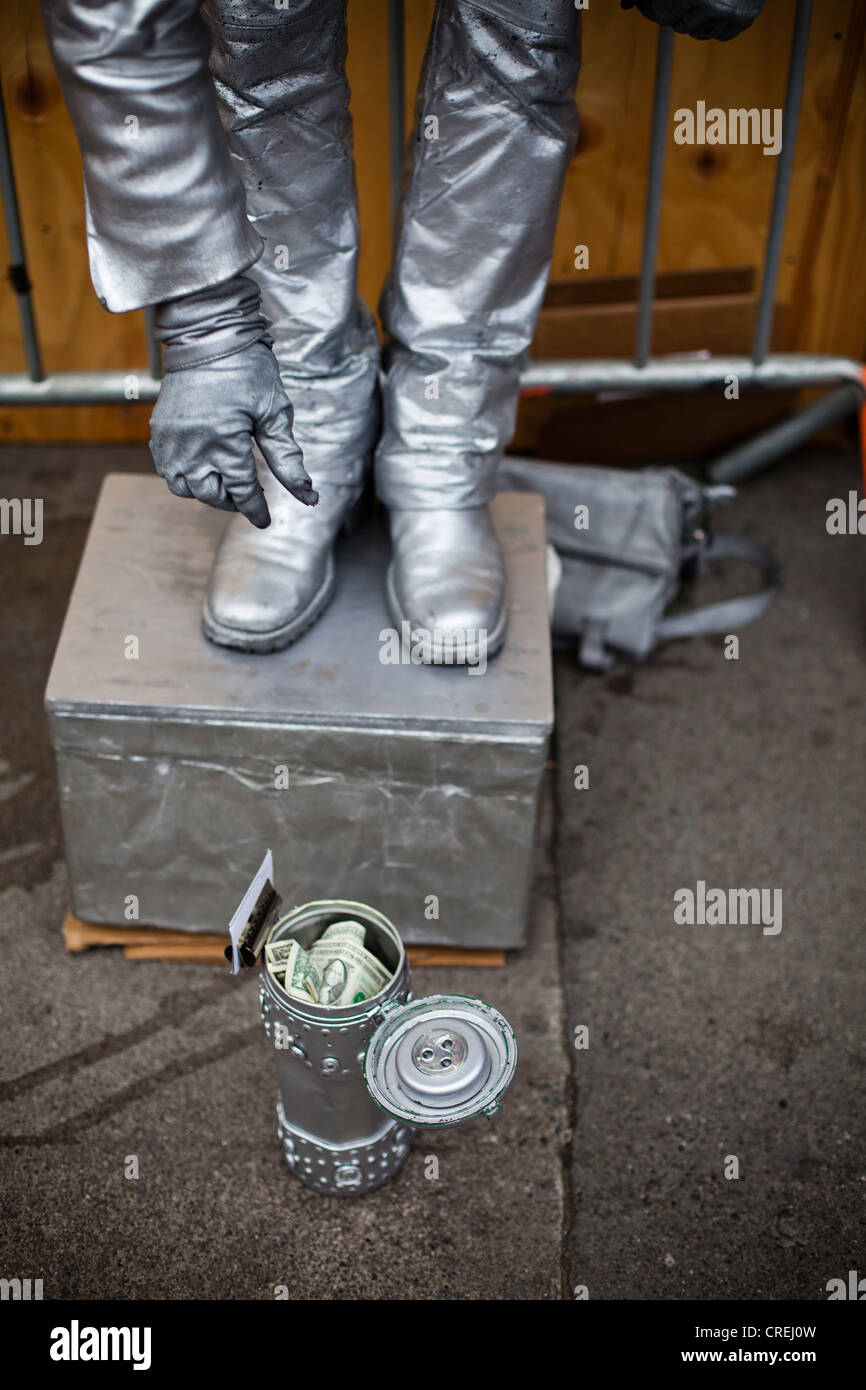 A street performer dressed in all silver drops a dollar bill into a can. - Stock Image