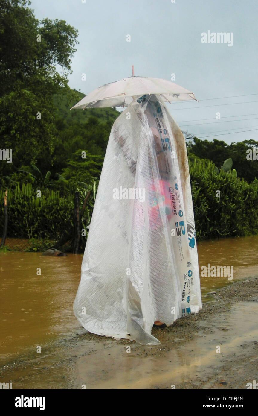 woman with umbrella and plastic rain cape, Cuba, Santiago de Cuba Stock Photo