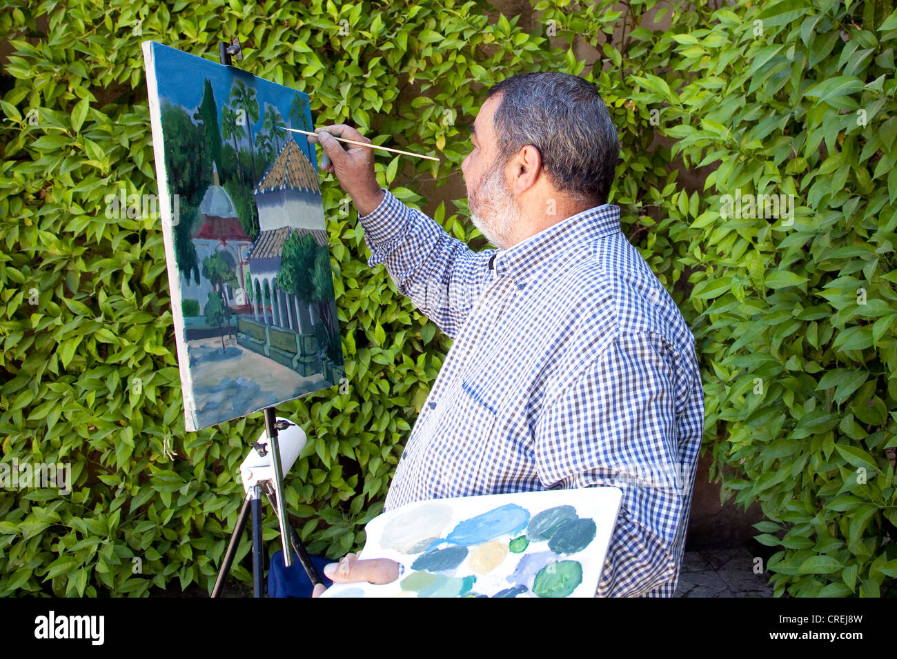 Painter painting an oil painting of garden architecture in the gardens of the Moorish King's Palace of Real Alcazar Stock Photo
