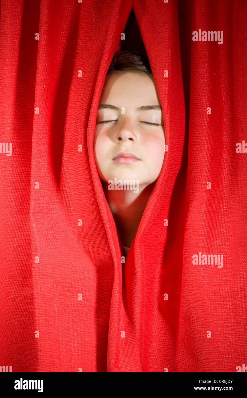 Red curtains on stage with face peering through - Stock Image
