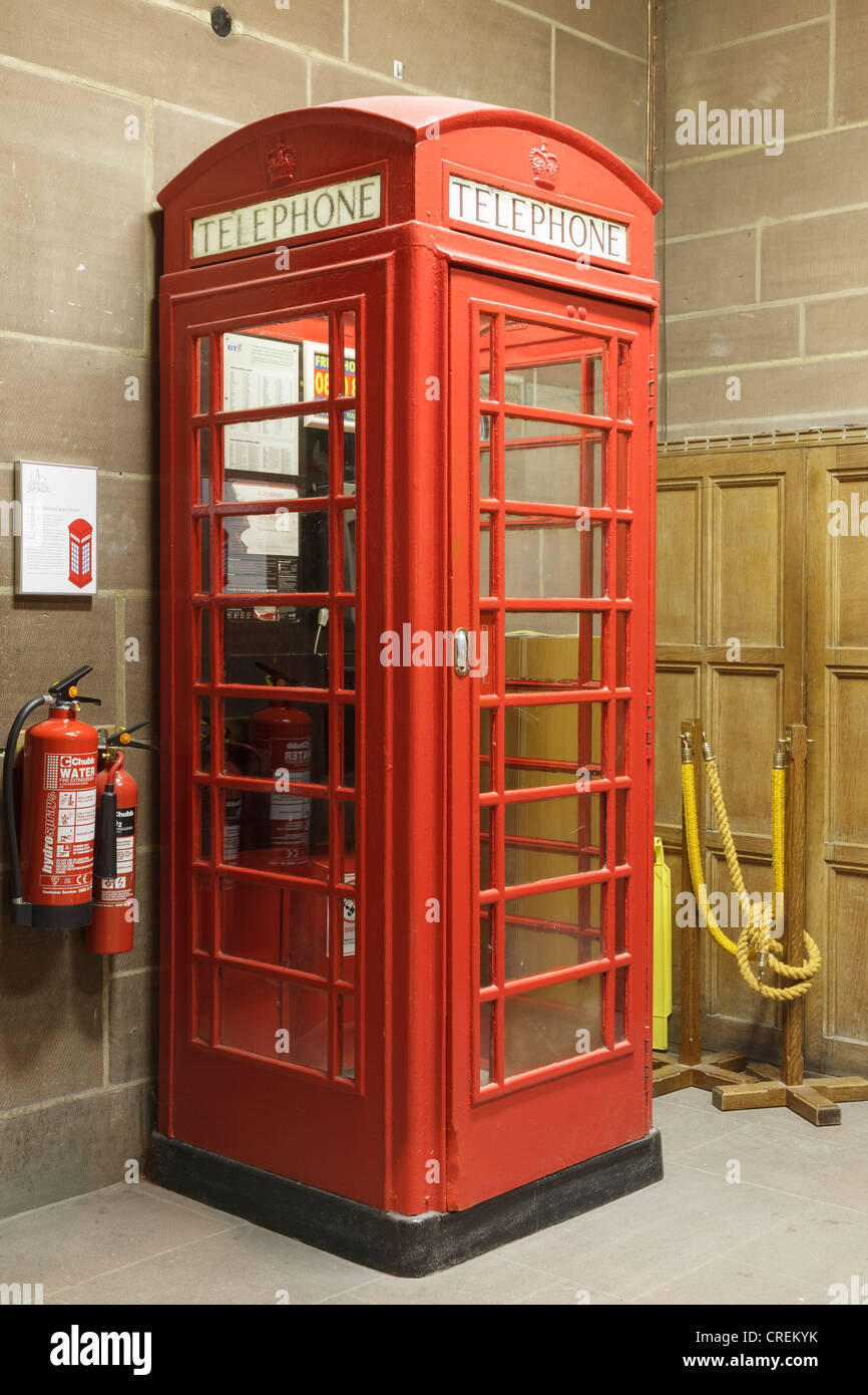 Old K6 cast iron red telephone box designed by Sir Giles Gilbert Scott in Liverpool Anglican cathedral. Merseyside, - Stock Image