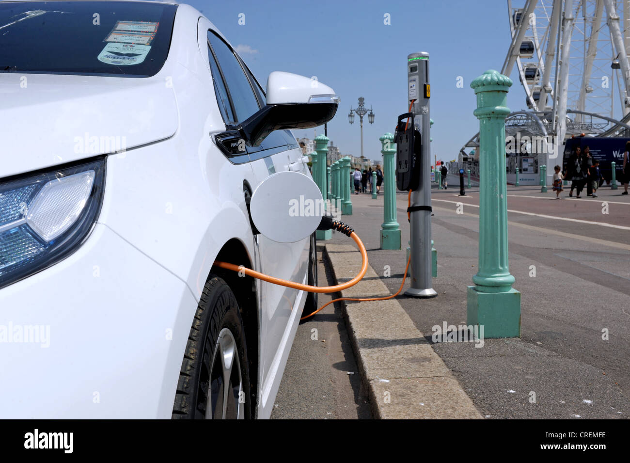 Car plugged into electric power charging point Brighton seafront UK Stock Photo