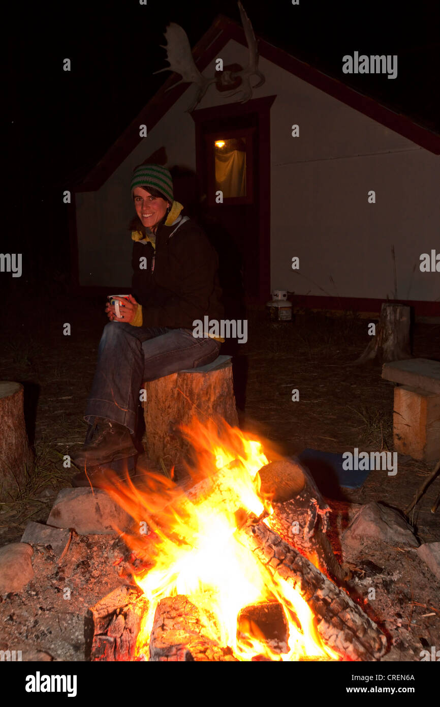 Young woman sitting at a camp fire, bonfire, holding a cup, illuminated wall tent, cabin with moose antlers behind - Stock Image