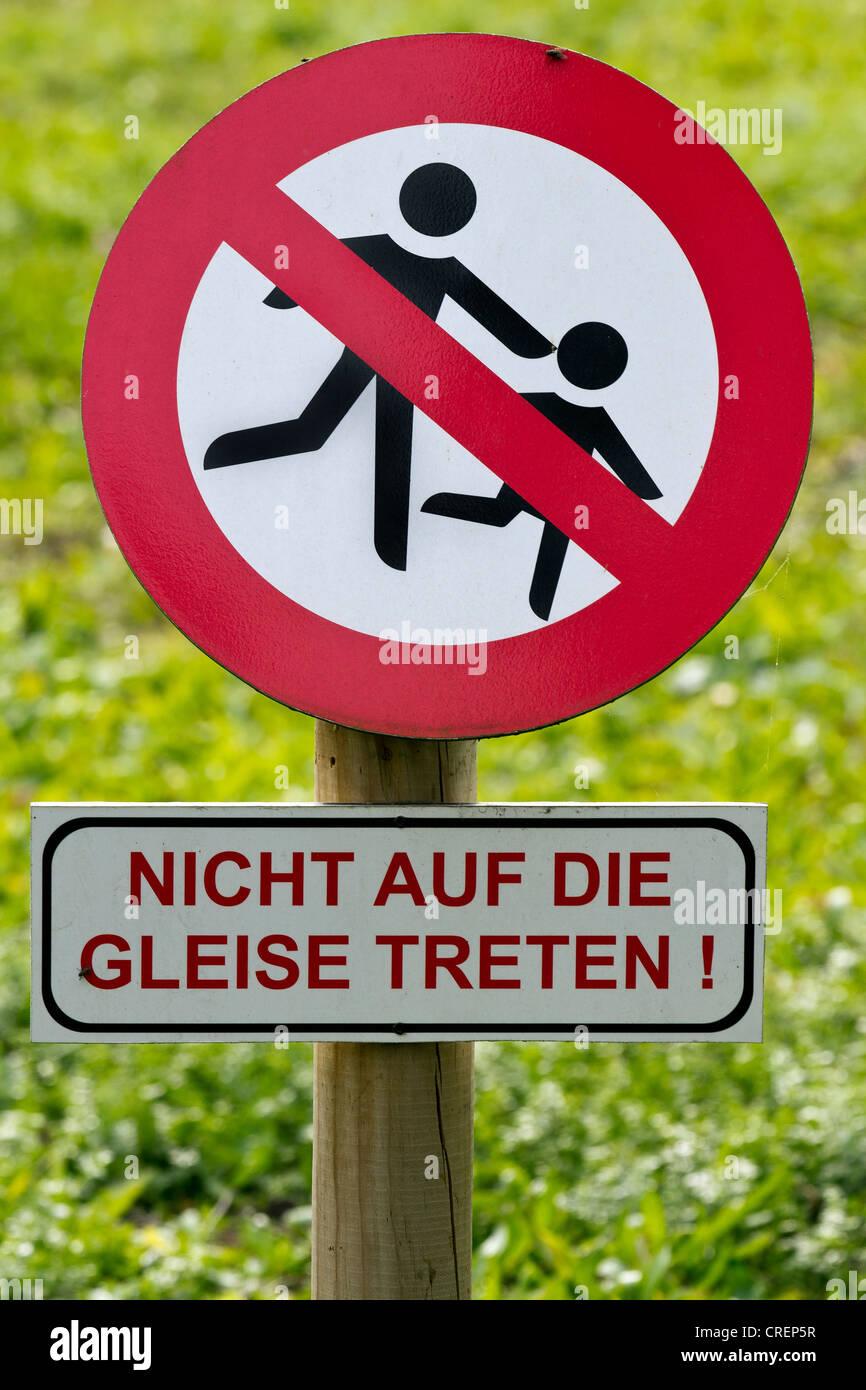 Prohibition sign, lettering 'Nicht auf die Gleise treten', German for 'Do not walk on the train tracks' - Stock Image