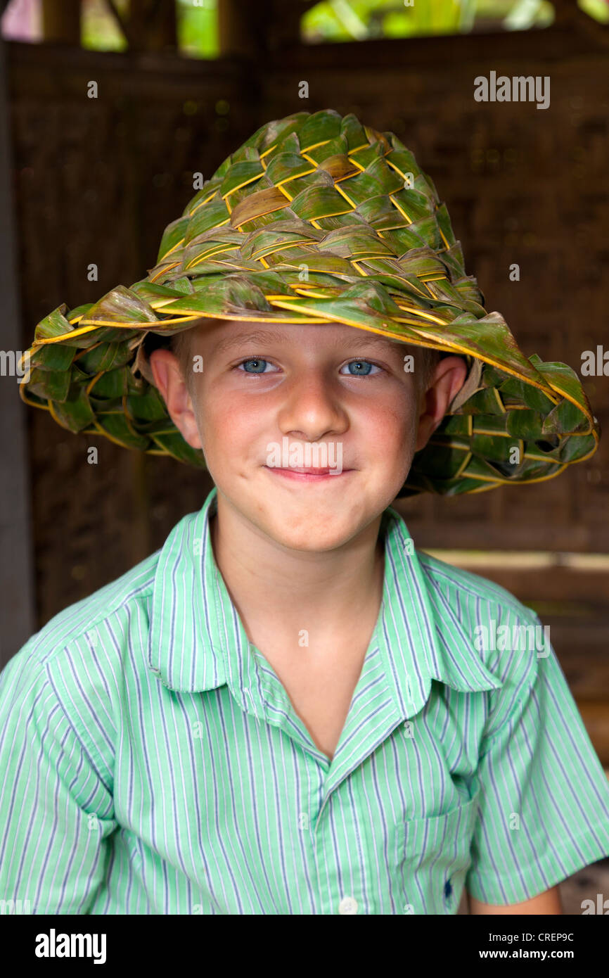 Boy wearing a hat made of woven leaves, near Ubud, central Bali, Bali, Indonesia, Southeast Asia - Stock Image