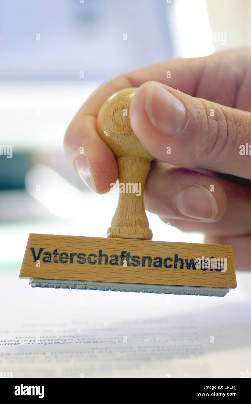 hand with a stamp Vaterschaftsnachweis, paternity proof - Stock Image