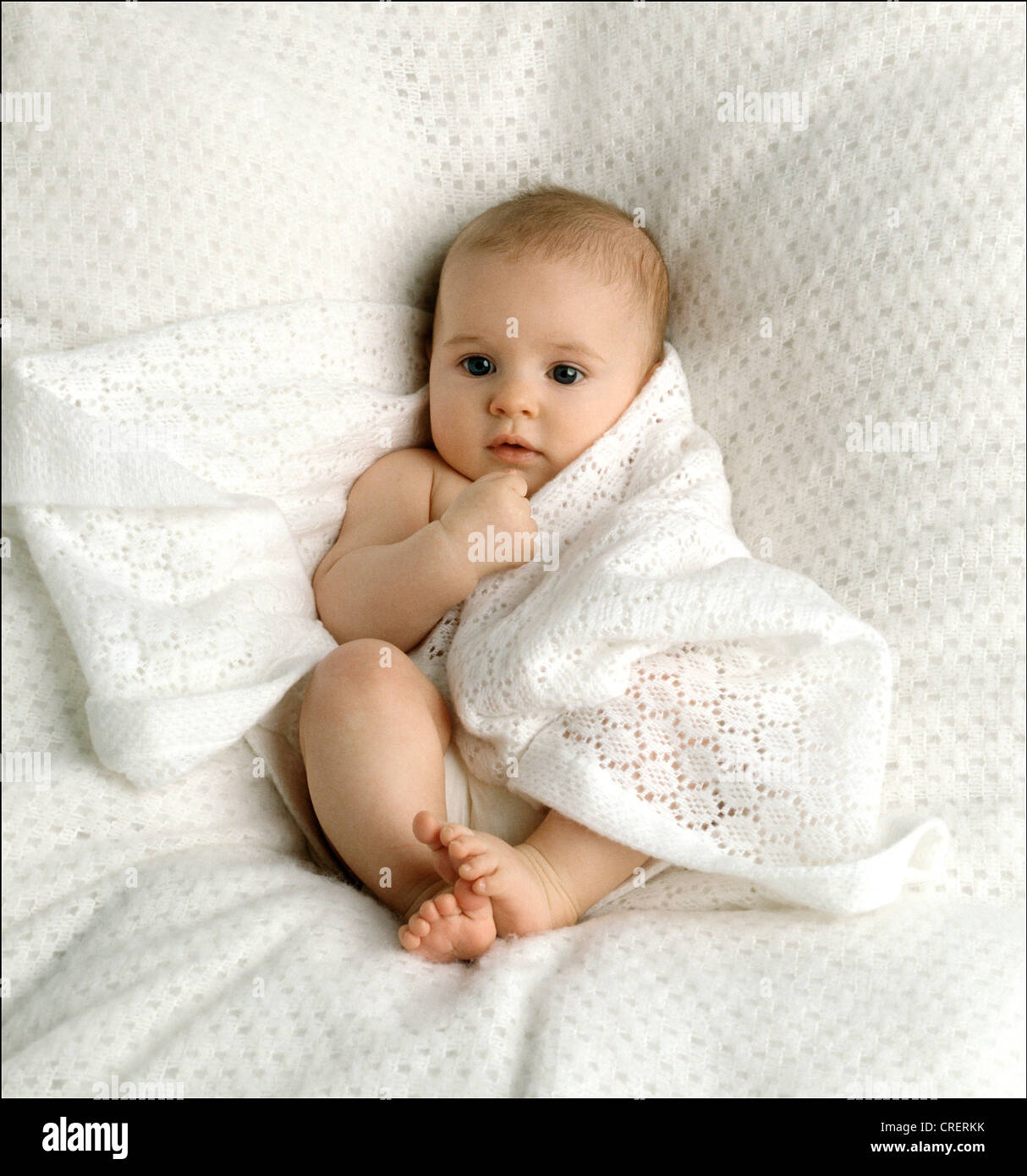 Contented Sleepy 6 Month Old Baby In Nappy Lying On Soft White Blanket Wrapped Shawl