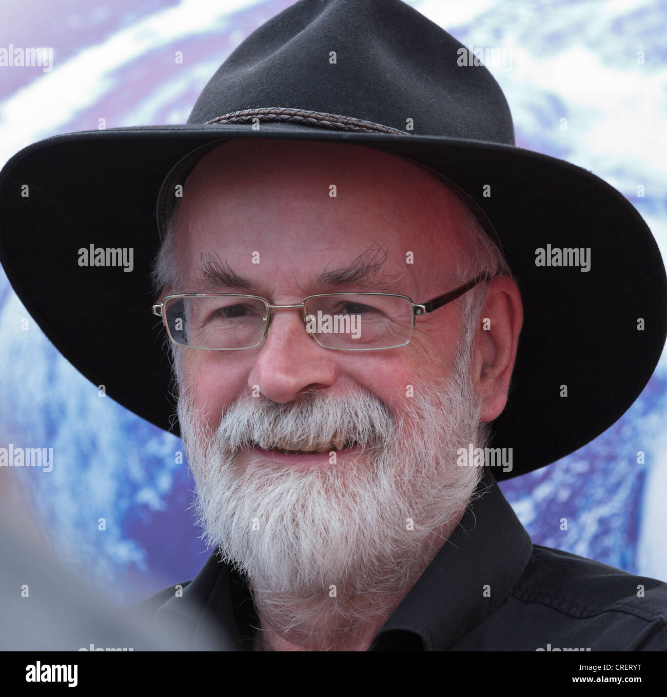 Sir Terence, John, David, (Terry) Pratchett OBE June 2012 with a giant inflatable globe behind - Stock Image