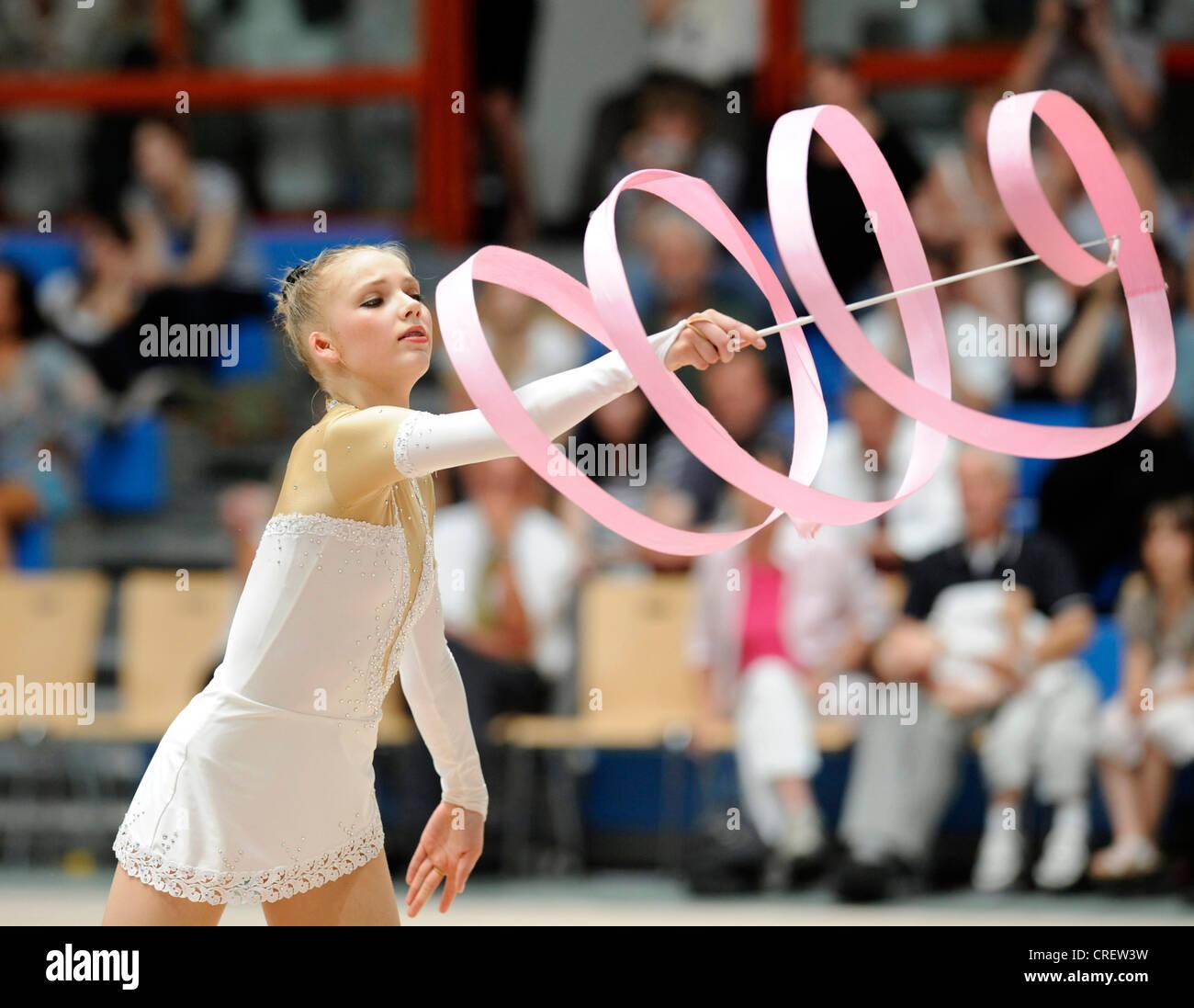 woman doing rhythmic gymnastics with ribbon - Stock Image