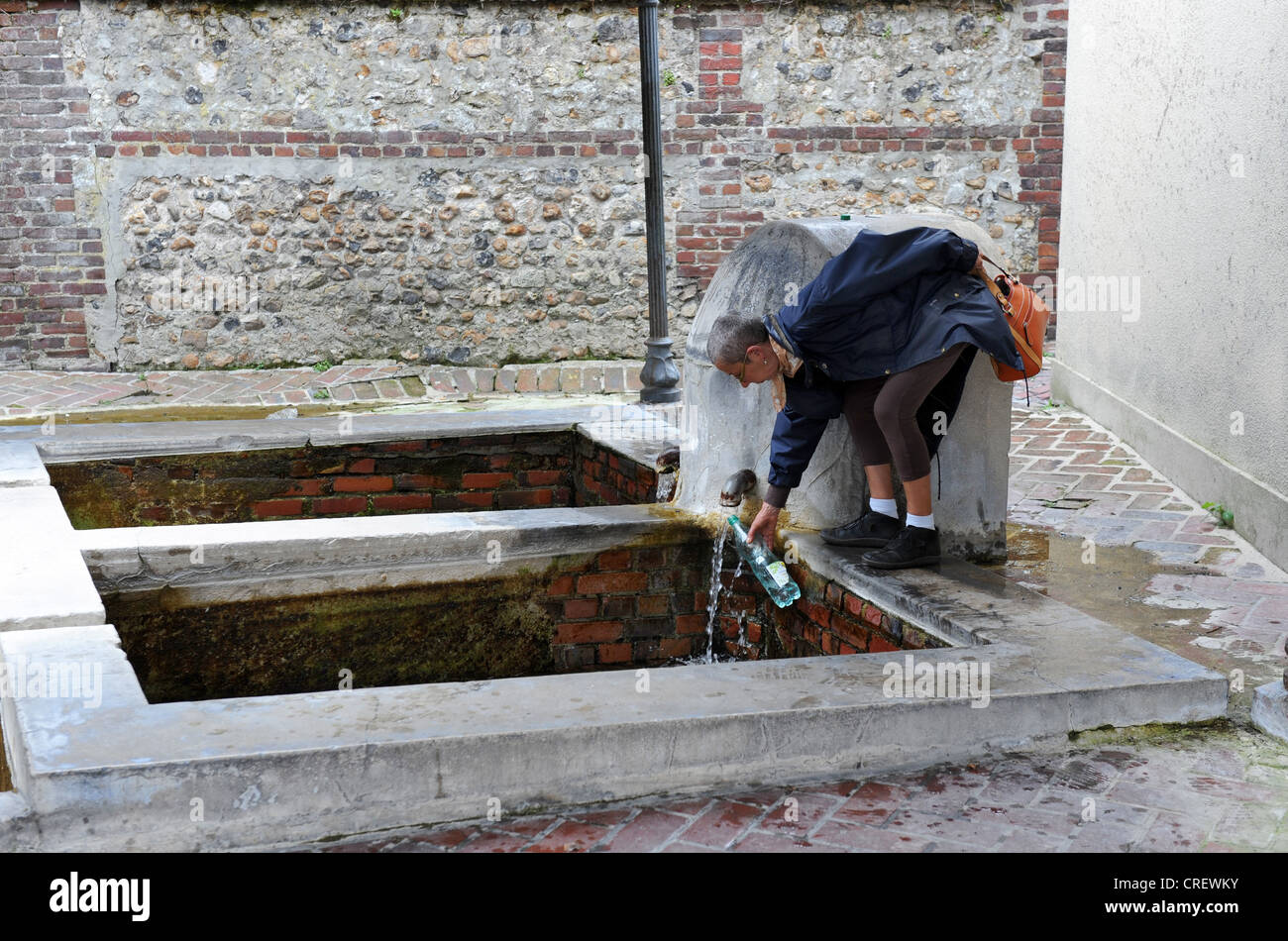 Woman filling bottle with spring water at the Lavoir in Honfleur Normandy France - Stock Image