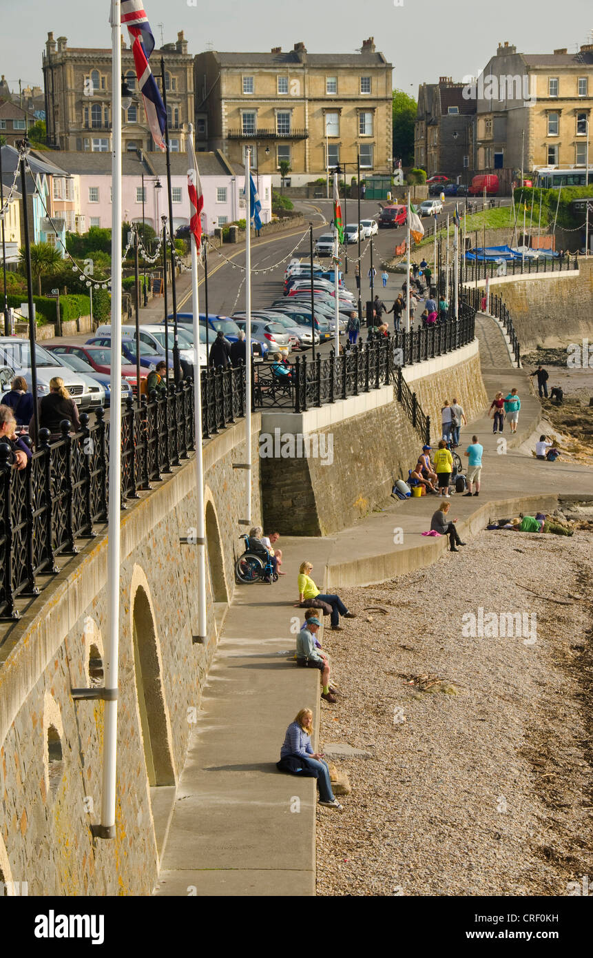 People walking along promenade and sitting on the walkway, Clevedon seafront, North Somerset, United Kingdom, UK, - Stock Image