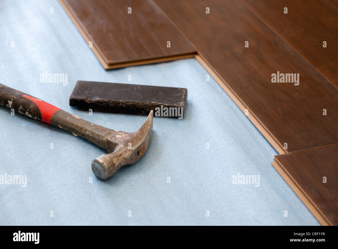 Hammer and Block with New Laminate Flooring Abstract. - Stock Image